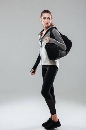 Full length portrait of a young fitness woman holding sports bag and looking away while standing isolated over gray background