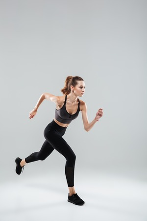 Vertical image of Sport woman running in studio over gray background Stock Photo