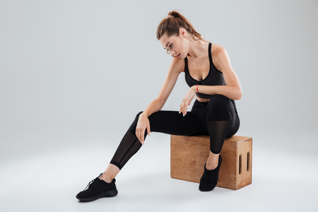 Sport woman relaxing on box in studio over gray background