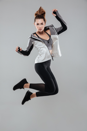 Full length portrait of a young healthy woman in sportswear jumping and looking at camera isolated over gray background Stock Photo