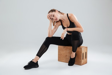 Tired Sport woman relaxing on box in studio over gray background