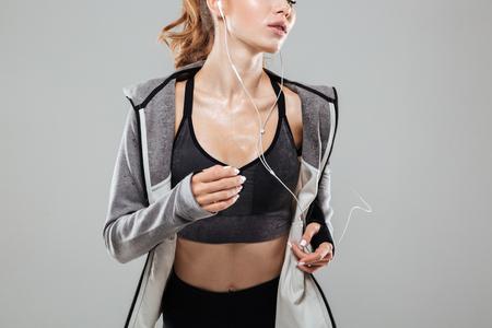 灰色の背景の上に孤立した中にイヤホンで音楽を聴くスポーツ ウエアで汗をかくフィットネス女性のトリミングされた画像