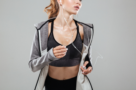 Cropped image of a sweaty fitness woman in sportswear listening to music with earphones while running isolated over gray background