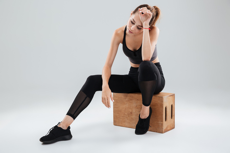 Tired Young Sport woman relaxing on box in studio ober gray background