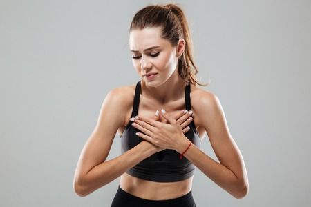 Young sportswoman having a chest pain while standing isolated over gray background Stock Photo