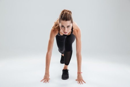 Young sport woman preparing to run over gray background Stock Photo