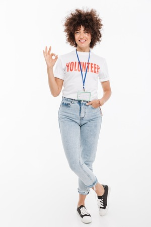 Happy smiling volunteer woman wearing badge standing and showing ok gesture isolated over white background