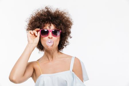 Positieve jonge vrouw in zonnebril die bellen blazen terwijl het kauwen van een gom die over witte achtergrond wordt geïsoleerd Stockfoto