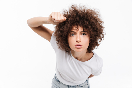 Ypung casual woman with curly hair knocking on the camera isolated over white background