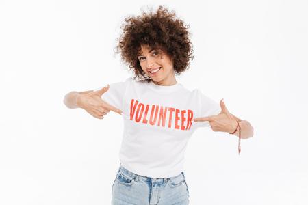 白い背景に孤立したボランティア t シャツで2本の指を指しているカジュアルな女性の笑顔