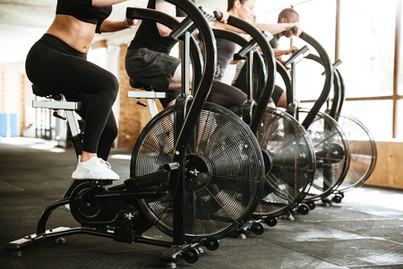 Cropped picture of group of multiethnic sports strong people make sport exercise with spinning bicycles. Reklamní fotografie