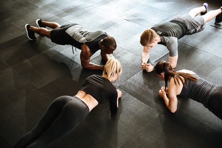 Image of fitness group of people make sports exercise indoors.