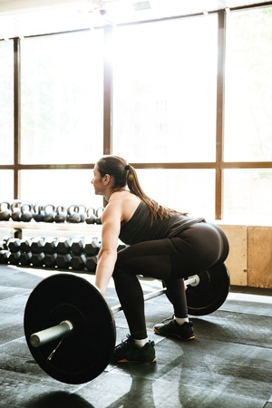Picture of sports strong woman make sport exercise with barbell.