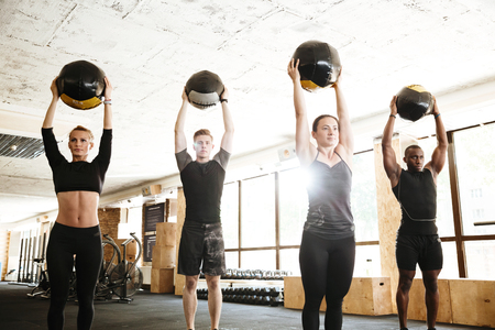 Image of group of serious sports strong people make sport exercise with ball. Looking aside.