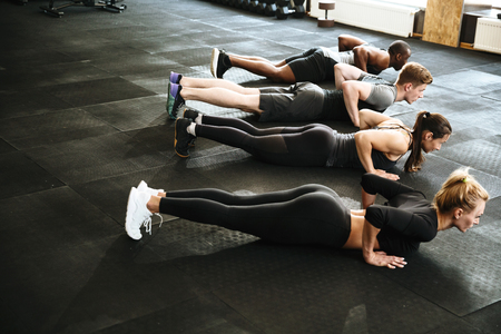 Group of young healthy people doing plank exercise together at the gym Stok Fotoğraf
