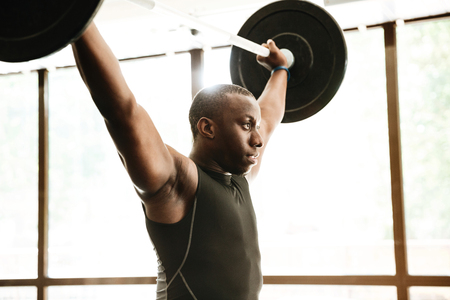 Image of african sports strong man make sport exercise with barbell.