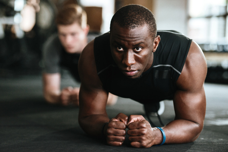 Picture of group of multiethnic sports strong people make sport exercises in gym.