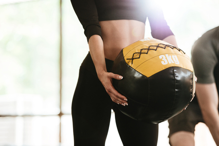 Cropped image of caucasian sports strong woman make sport exercise with ball.
