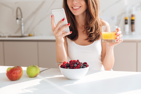 Cropped image of smiling pretty woman looking at mobile phone and holding glass of orange juice while having breakfast in a kitchen