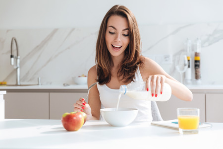 Happy joyful woman pouring milk into a bowl while sitting and having breakfast at the kitchen table