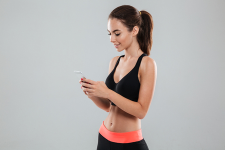 Side view of a smiling fitness woman using smartphone over gray background Stock Photo