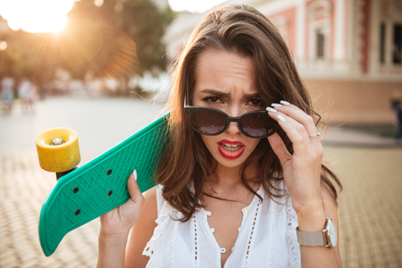 Image of confused young woman holding skateboard outdoors. Looking camera. Stock Photo