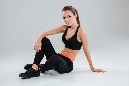 Happy Fitness woman relaxing on the floor in studio and looking at the camera over gray background