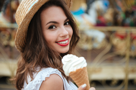 turnabout: Close up portrait of a smiling pretty girl with ice cream standing in front of the carousel at the amusement park