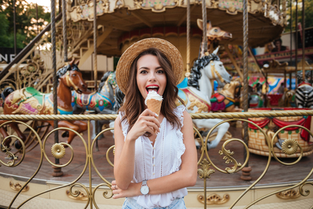 turnabout: Happy pretty girl eating ice cream while standing in front of the carousel at the amusement park