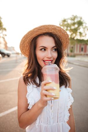 Picture of beautiful young woman outdoors drinking juice. Looking aside. Stock Photo