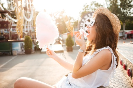 Side view of a young girl in sunglasses eating cotton candy at amusement park