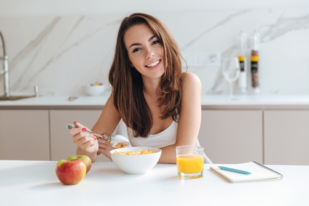 Smiling healthy woman eating corn flakes cereal while sitting and having breakfast at the kitchen table Stock Photo