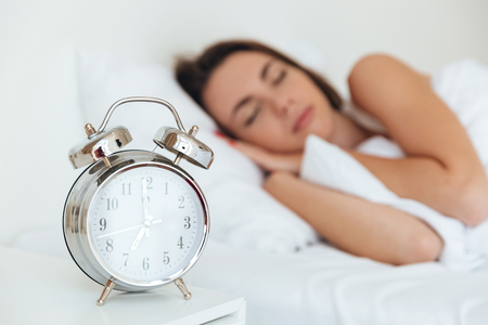 Close up portrait of an alarm clock with sleeping woman in bed on a background