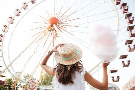 Vue arrière d & # 39 ; une jeune fille dans le chapeau tenant des bonbons de coton debout dans la grande roue à l & # 39 ; hôtel parc Banque d'images - 86207962