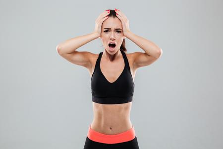 彼女の頭を押し、灰色の背景の上のカメラを見てショックを受けたスポーツ女性