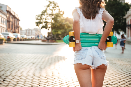 Cropped picture of young woman with skateboard walking outdoors.