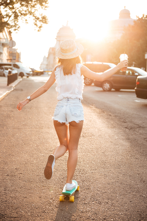 Back view image of young woman outdoors walking with skateboard.