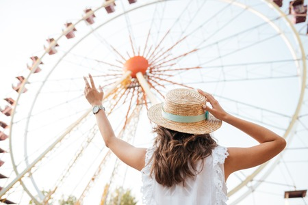 Back view of a young girl in hat standing at the ferris wheel at the amusement park