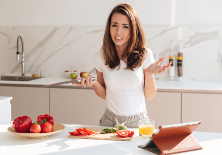 Confused young woman holding knife and shrugging shoulders while cooking on a kitchen Stock Photo