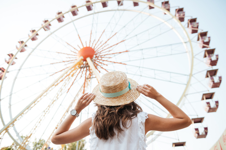 Back view of a young girl in hat standing in front of the ferris wheel at the amusement park Stock Photo