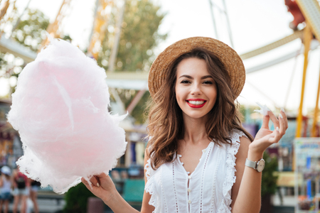 Happy smiling girl with cotton candy at the amusement park Stok Fotoğraf