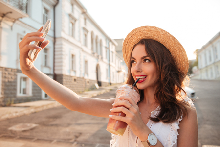 Photo of pretty young woman outdoors make selfie by phone drinking juice. Looking aside.