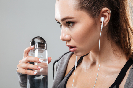 Close up side view of sports woman with water listening music over gray background Stock Photo