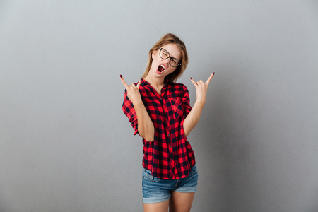 Photo of amazing young blonde woman wearing glasses standing isolated over grey wall showing rock gesture.