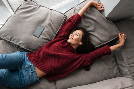 Top view of a smiling beautiful asian woman in sweater lying on a couch at home with blank screen mobile phone and stretching hands