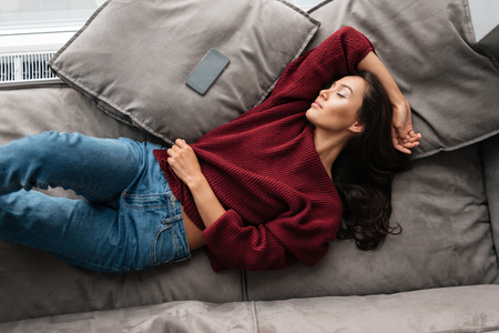 Top view of a smiling asian woman in sweater sleeping on a couch at home with blank screen mobile phone