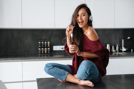 Glückliche junge asiatische Frau in den Kopfhörern , die Nachtisch mit einem Löffel eines Glases in einer Küche isst Standard-Bild