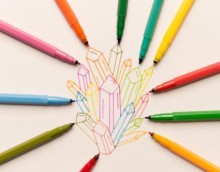 紙の上の異なるマーカー間に描かれたカラフルな結晶のグループ