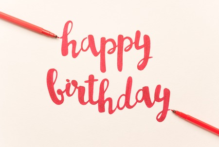 Inspirational phrase Happy birthday for greeting cards and posters drawing with red marker on white paper 스톡 콘텐츠