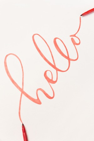 Greeting phrase Hello handwritten with orange marker on white paper